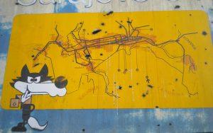 Zerschossenes Olympiaschild mit Maskottchen Vucko in Sarajevo