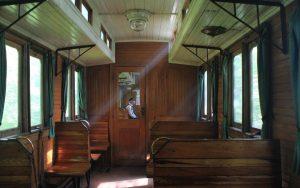 Zugbegleiter sitzt in historischem Holzwagon