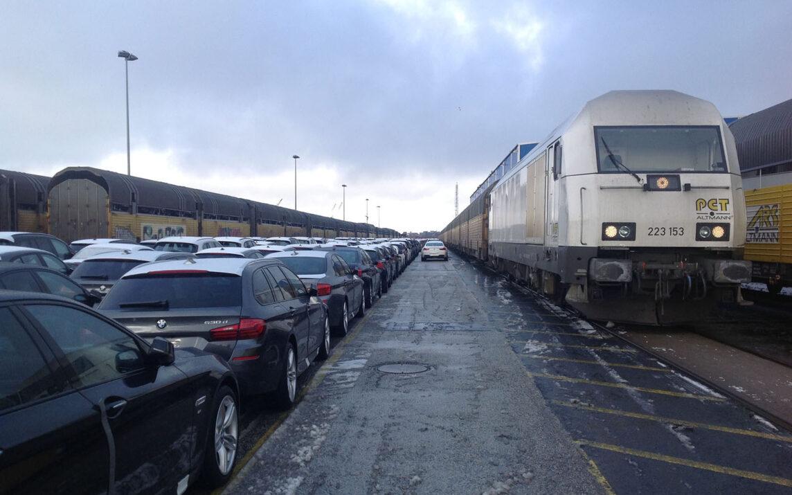 Cuxhaven, BHF und Hafen: Neuwagen werden zur Entladung im Hafen aufgereiht. PCT Altmann 223153 wartet auf Nebengleis.