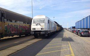 Baureihe 223 in Bremen Rangierbahnhof ankommend, fabrikneue Autos warten auf Transport auf der Schiene