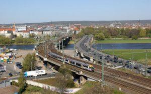 Blick auf eine Elbbrücke in Dresden mit einem Triebwagen der Städtebahn Sachsen