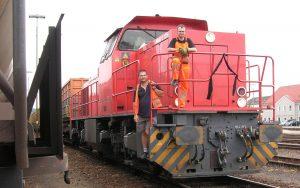 Railmen Lokführer in orangener Warnkleidung stehen auf einer Lok
