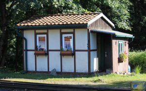 Kleine Laube mit zwei Blumenverzierten Fenstern an den Bahngleisen