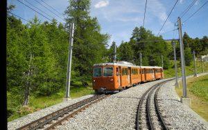 Die orangene Gornergratbahn von Zermatt fährt auf den typischen Zahnradgleisen.