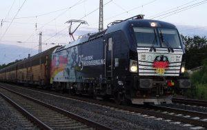 Eine für den Tag der Deutschen Einheit lackierte Siemens VECTRON der Eisenbahnlogistikers MRCE vor einem Autozug der PCT Private Car Train GmbH (PCT)