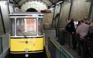 Dresdner Standseilbahn fährt in die Talstation ein während Fahrgäste an der Seite warten.