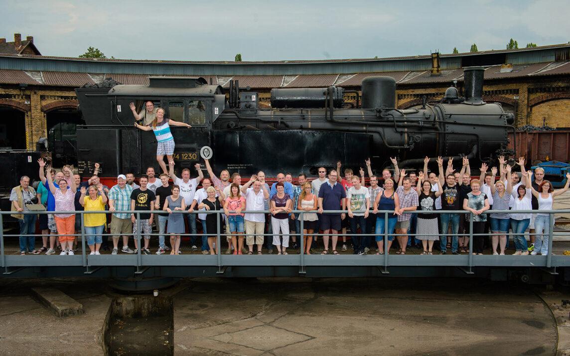 Das Railmen Team Gruppenfoto im BW Schöneweide vor alter Dampflok beim railmen-Tag 2015.