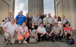 Railmen Mitarbeiter posieren zusammen für ein Gruppenbild unterm Brandenburger Tor.