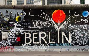 Mauerkunst. Der Berlin-Teil, der East-Side-Gallery, mit weißer Typografie auf schwarzem Grund und rotem Ballon.