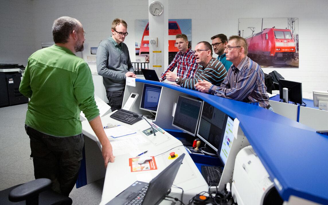 Lokführer Kollegen stehen im Trainingszentrum um den Tresen und hören gespannt den Auswertungen des Ausbilders zum Ihrem Simulator-Training zu.