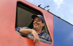 Lokführer mit Basecap und Schnautzer schaut verschmitzt aus Fenster einer Lok.