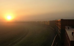 Ein langer Güterzug bahnt sich den Weg durch die reizvolle Morgenstimmung über der Ebene bei Neuburg an der Donau
