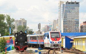Jekaterinburg mit Parkeisenbahn von einer modernen Diesel-Lokomotive gezogen. Links daneben eine alte deutsche Dampflok aus den 30er Jahren.