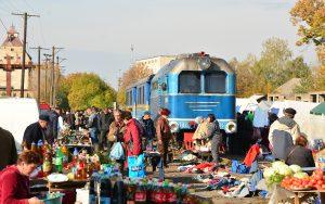 Markttrubel auf den Gleisen von Vinogradov in der Ukraine während sich die blaue Schmalspurbahn nähert.