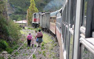 Der Tren Macho in Peru fährt an einer Familie mit Kind vorbei.