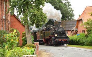 Dampfende Schmalspurbahn fährt durch kleine Siedlung aus Backsteinhäusern.