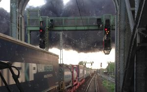 Güterzug überquert Brücke die von einer riesigen grauen Dampfwolke überspannt wird