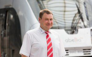 Triebfahrzeugführer posiert in weißem Hemd und roter Krawatte vor abellio Zug
