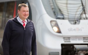 Bahnpersonal steht am Gleis lächelnd vor Personenzug