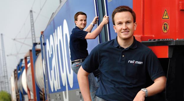 Junger Lokführer steigt in den Führerstand eines Güterzuges