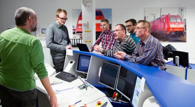 Ausbilder beantwortet während der Weiterbildung den Lokführern Fragen.