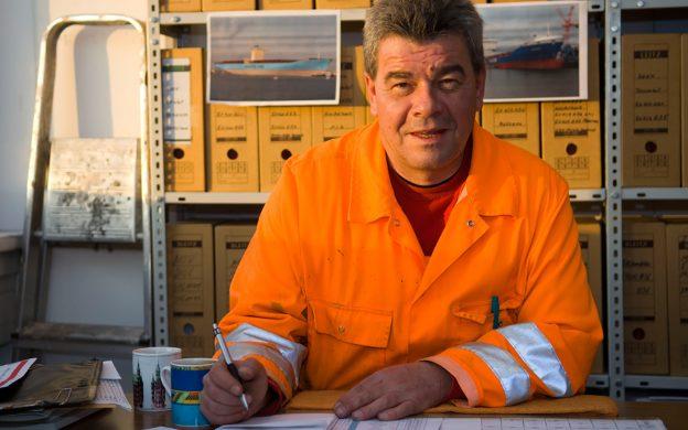 Wagenmeister in Warnjacke sitzt am Schreibtisch im Büro vor einem Regal mit Aktenordnern.