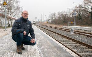 Railmen-Lokführer Jan Krehl posiert hockend am Bhf Grimma.