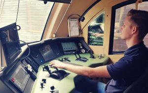 Triebfahrzeugführer sitzt im Führerstand und bedient die Steuerhebel