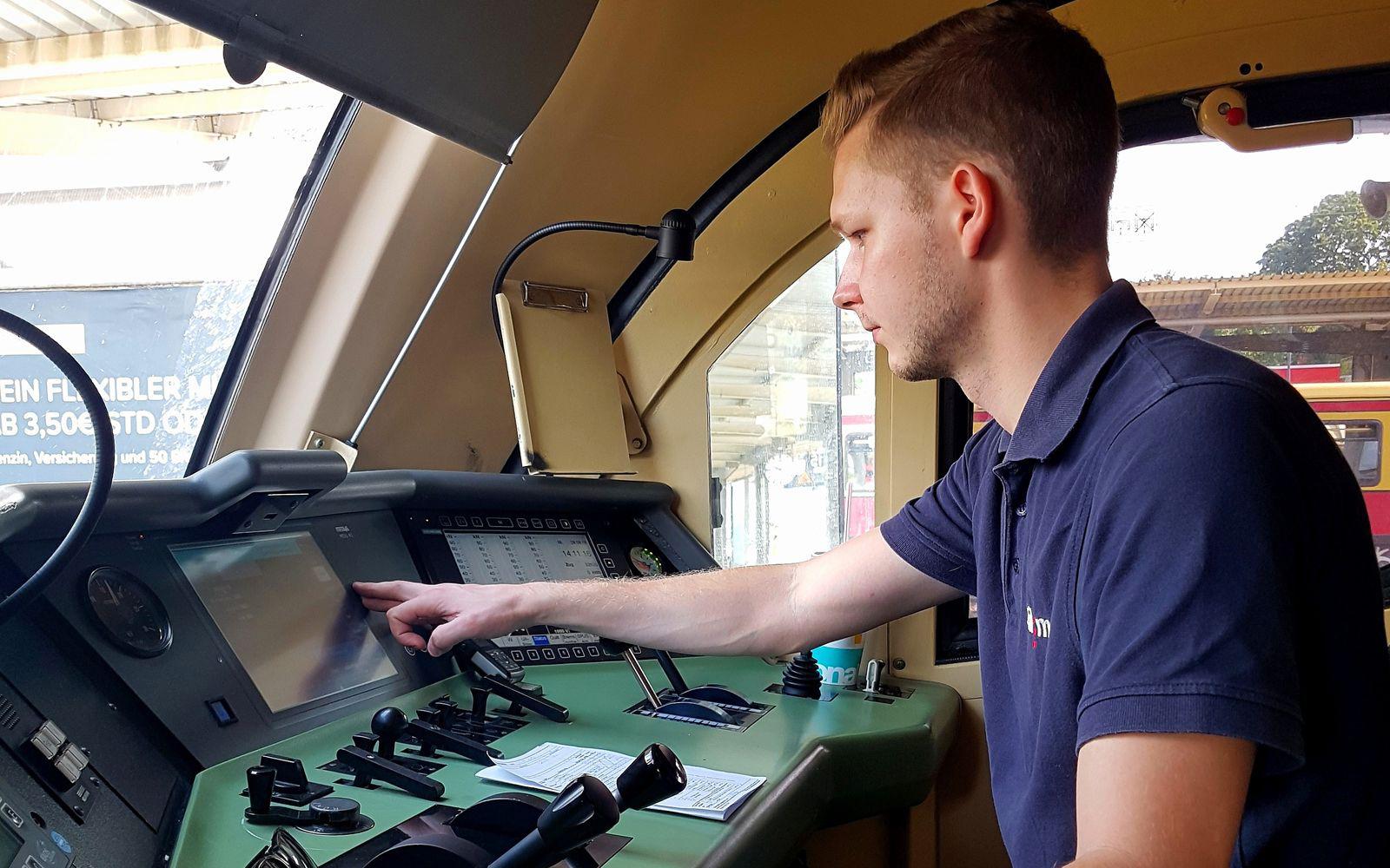 Railmen Tf sitzt im Führerstand und prüft am Monitor den Streckenplan