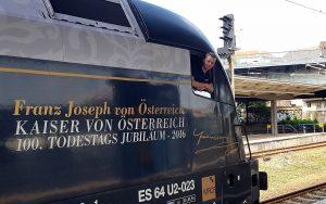 ÖBB Triebwagen mit Lokführer der durch das Fenster in die Kamera lächelt