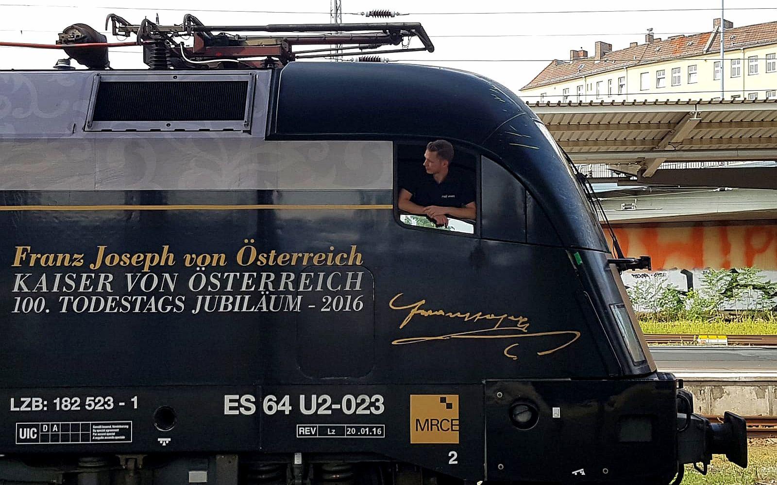 Triebfahrzeugführer beim Kontrollblick aus dem Führerstand eines schön gestalteten Triebwagen zum 100. Todestag von Franz Joseph, dem Kaiser von Österreich